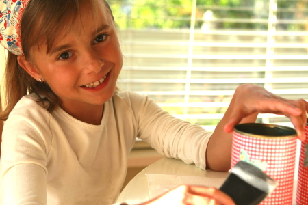 Little girl applying Mod Podge to the can sealing the decorative paper that has been applied to the can.