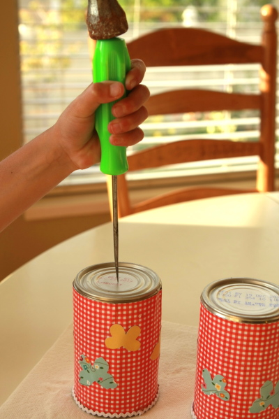 Punch a hole in the bottom of the can using a hammer and awl or nail. The hole must be large enough to put string through.