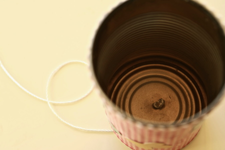 Insert a long piece of string through the hole in the can and tie a knot in the string on the inside of the can.