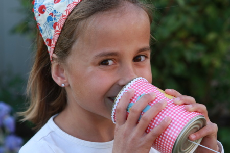 Little girl talking into the can phone - can you hear me?
